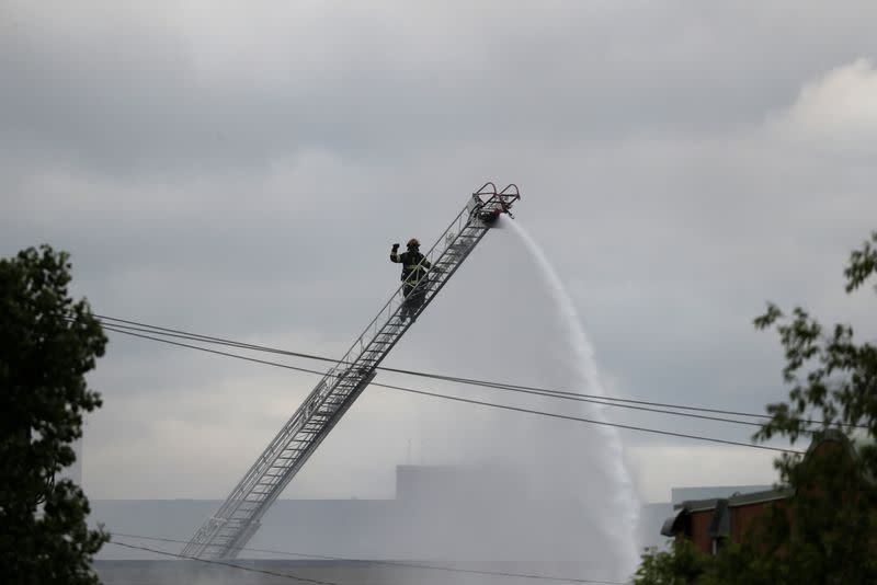 A firefighter is seen in a ladder while putting out a fire in a store in the aftermath of a protest in Minneapolis