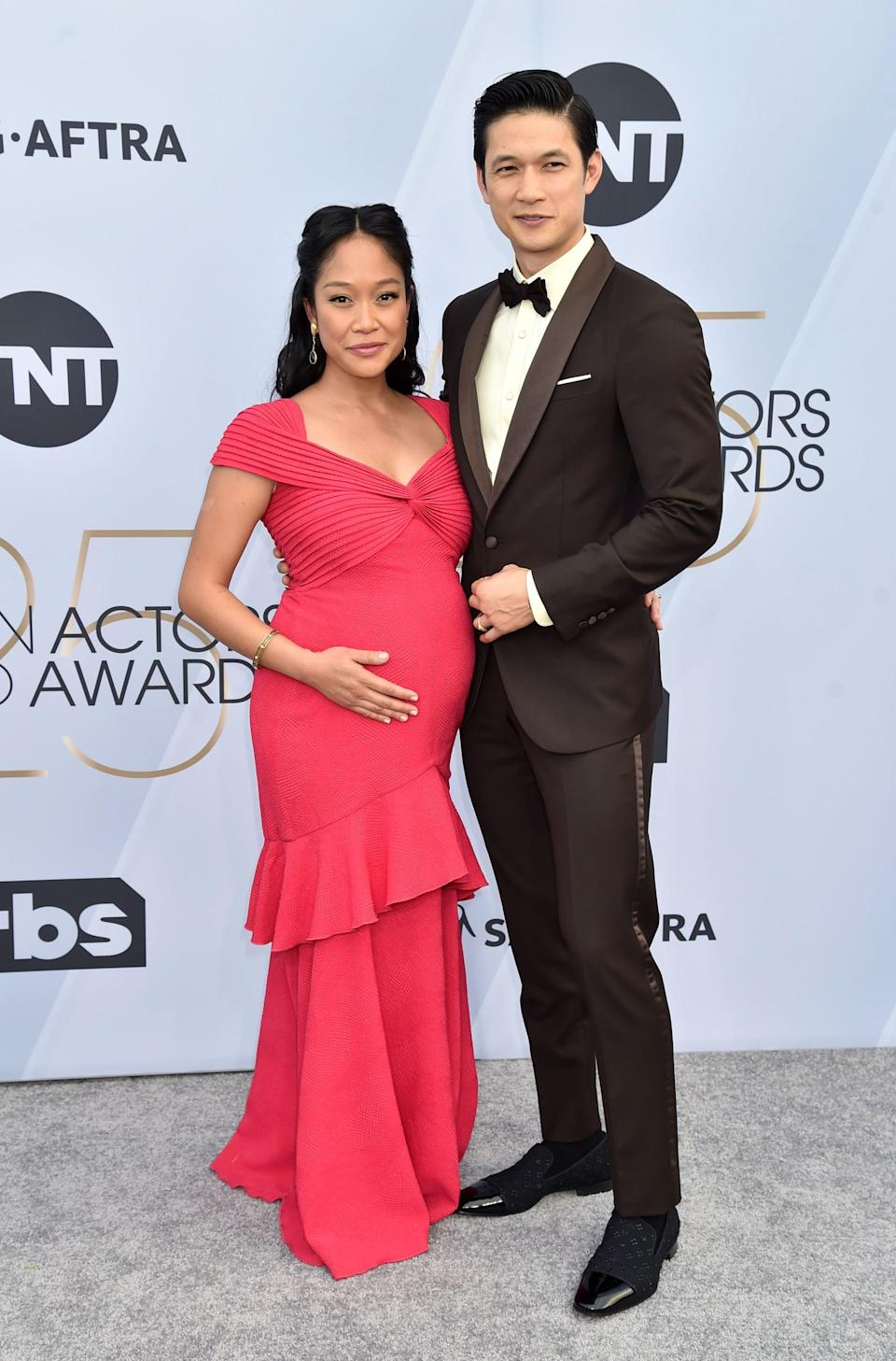 <p>Harry wearing a black suit with a Chopard watch. Shelby wearing a pink ruffled gown.</p>
