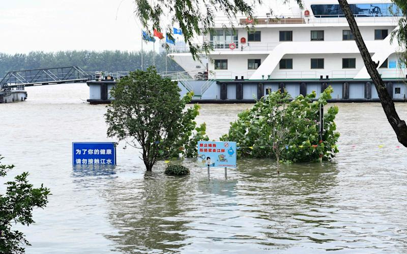 Signs are submerged in floodwaters on the bank of the Yangtze River in Nanjing in China's eastern Jiangsu province - AFP