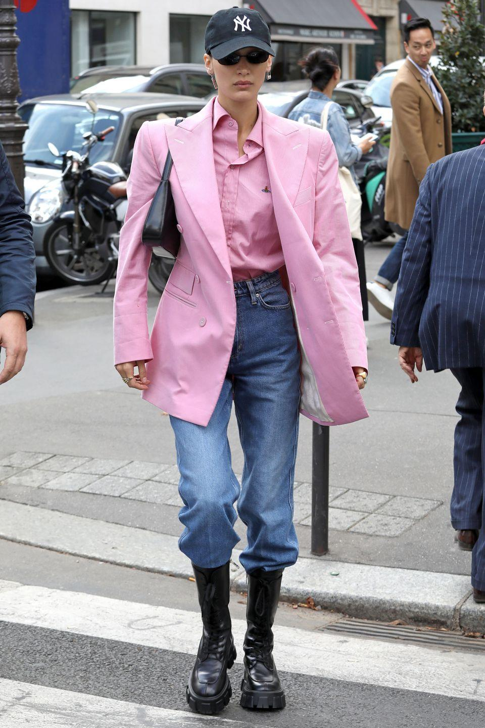 <p>In a pink Vivienne Westwood shirt and blazer with high-waisted jeans, Prada boots and a New York Yankees baseball cap. <br></p>