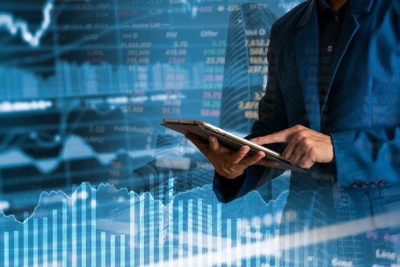 Man holding a tablet in front of stock prices and graphs.