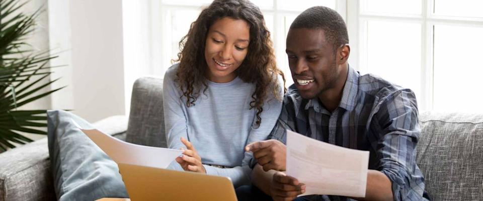 Couple sitting on sofa reviewing mortgage rates