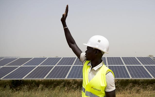 A worker at a solar plant in Senegal - one of the biggest in Africa - Bloomberg