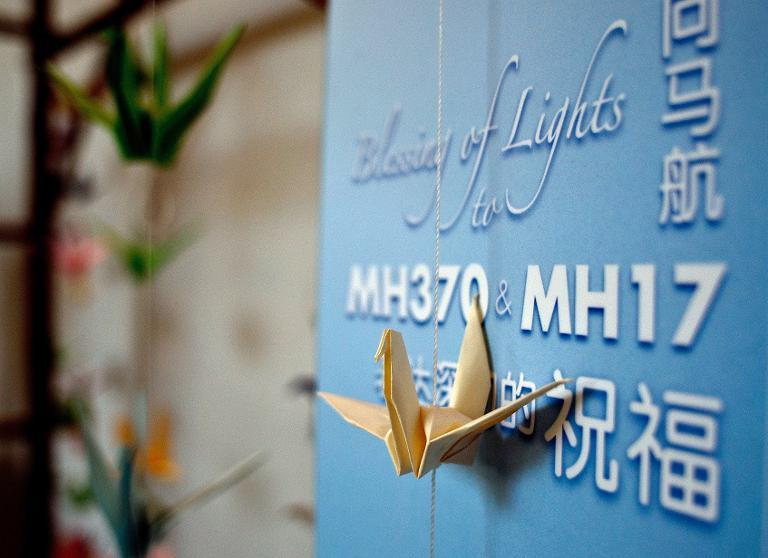 Origami paper cranes hang on a board offering prayers and condolences to the Malaysia Airlines MH370 and MH17 victims and their families at a Chinese bereavement centre in Kuala Lumpur on September 9, 2014