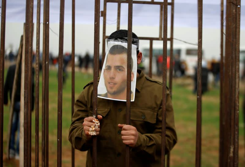 FILE PHOTO: Palestinian man playing the role of Israeli soldier Oron Shaul stands in a mock jail during a rally in solidarity with Palestinian prisoners held in Israeli jails, in the northern Gaza Strip