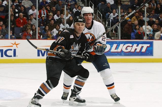 WASHINGTON - JANUARY 1: Adam Oates #17 of the Washington Capitals battles with defenseman Kenny Jonsson #29 of the New York Islanders during the game at the MCI Center in Washington D.C. on January 1, 2002. The Capitals defeated the Islanders 3-2. (Photo by Mitchell Layton/Getty Images/NHLI)
