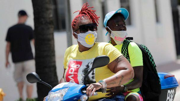 PHOTO: People wearing protective face masks ride a scooter down Ocean Drive during the coronavirus pandemic, July 12, 2020, in Miami Beach, Fla. (Lynne Sladky/AP)