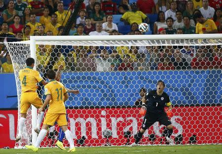 Australia's Tim Cahill (L) heads the ball to score a goal past Chile's goalkeeper Claudio Bravo (R) during their 2014 World Cup Group B soccer match at the Pantanal arena in Cuiaba June 13, 2014. REUTERS/Paul Hanna