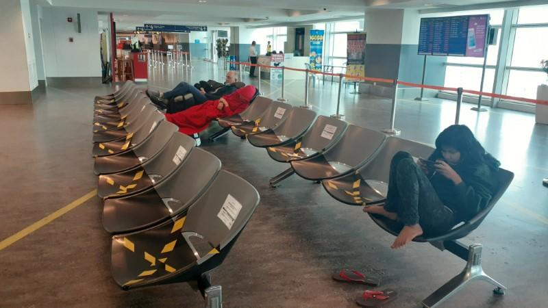 Stranded tourists sit in chairs at the transit area of Kuala Lumpur International Airport in Sepang