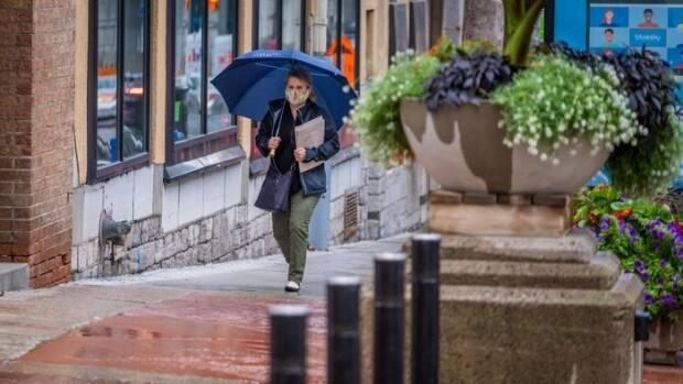 A pedestrian with a mask and umbrella walks in downtown Ottawa during the COVID-19 pandemic. (Michel Aspirot/Radio-Canada - image credit)