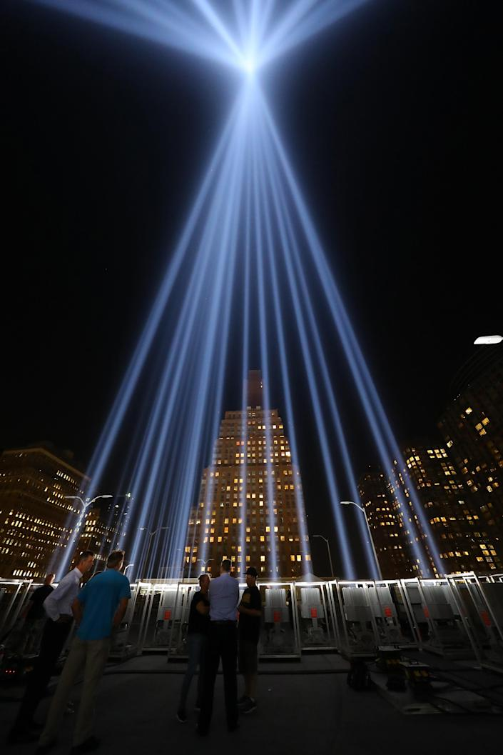 <p>Visitors watch as workers turn on the Tribute in Light — which rises above the New York City skyline from the rooftop where the memorial was installed — on Sept. 5, 2018. (Photo: Gordon Donovan/Yahoo News) </p>