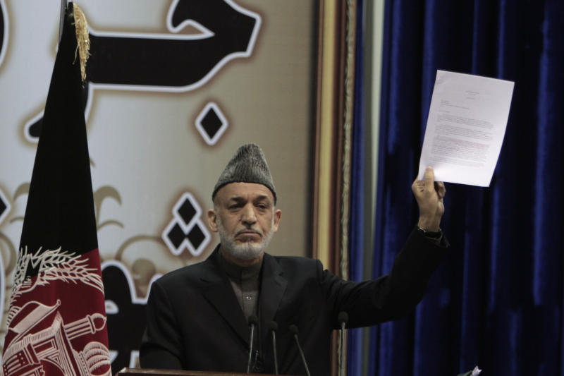 Afghan President Hamid Karzai holds a copy of a weekly security report during the last day of the Loya Jirga in Kabul, Afghanistan, Sunday, Nov. 24, 2013. Afghanistan's president says he won't immediately sign a security deal with the United States, ignoring a recommendation by an assembly of Afghan elders and leaders that he do so by the end of the year. (AP Photo/Rahmat Gul)