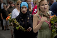 FILE - In this Sunday, July 24, 2011 file photo, women carry flowers as they arrive for a memorial service at Oslo Cathedral in the aftermath of the bombing and shooting attacks on Norway's government headquarters and a youth retreat, in Oslo. On the ten-year anniversary of Norway's worst peacetime slaughter, survivors of Anders Breivik's 22 July assault worry that the seam of racism that nurtured the anti-Islamic mass-murderer is re-emerging.Most of Breivik's 77 victims were teen members of the Labor Party Youth wing - idealists enjoying their annual camping trip on the tranquil, wooded island of Utoya. Today many survivors are battling to keep their vision for their country alive. (AP Photo/Emilio Morenatti, File)