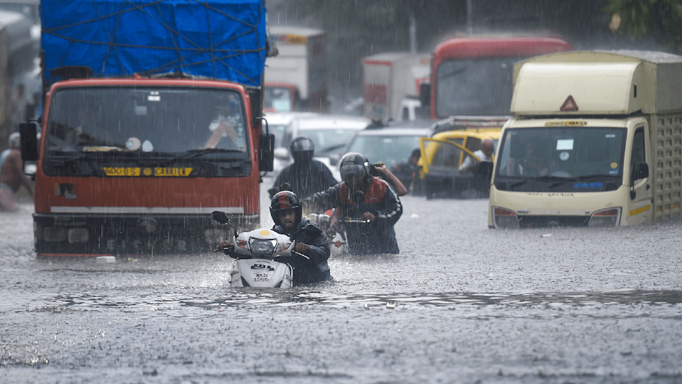 Vehicles ply through waterlogged a road due to heavy rain in Thane on 9 June.