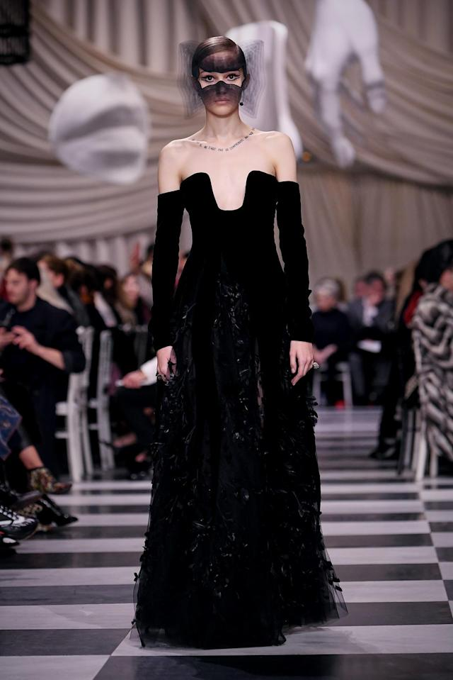 <p>Model wears a strapless, longsleeve black velvet gown and mask from the Dior Haute Couture SS18 collection. (Photo: Getty) </p>