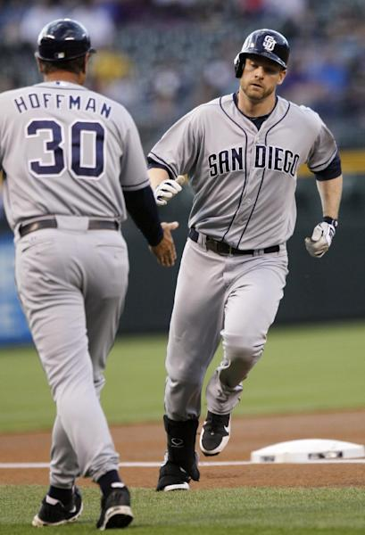 San Diego Padres third base coach Glenn Hoffman, left, congratulates Chase Headley as he rounds third base after hitting a solo home run off Colorado Rockies starting pitcher Juan Nicasio in the first inning of a baseball game in Denver on Wednesday, April 18, 2012. (AP Photo/David Zalubowski)