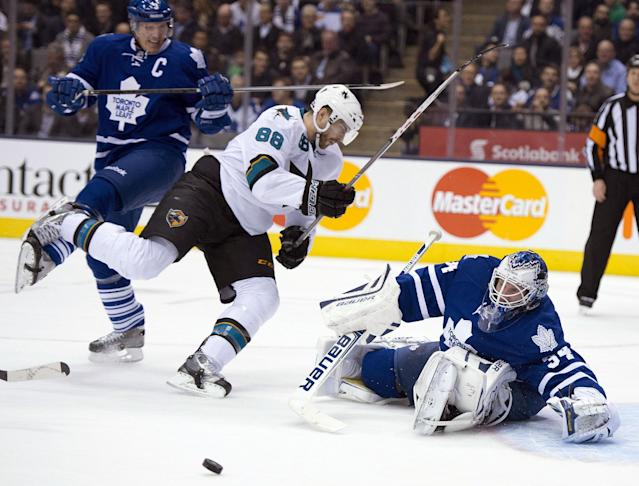 Toronto Maple Leafs' Dion Phaneuf (3) dumps San Jose Sharks right winger Brent Burns (88) as Leafs goaltender James Reimer makes a save during first period NHL hockey game in Toronto on Tuesday, Dec. 3, 2013. (AP Photo/The Canadian Press, Frank Gunn)