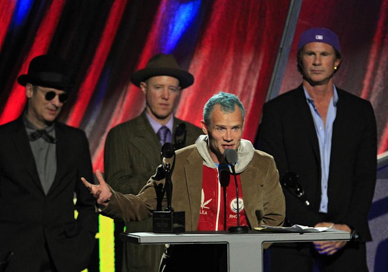 """Red Hot Chili Peppers' Mike """"Flea"""" Balazary speaks after induction into the Rock and Roll Hall of Fame Sunday, April 15, 2012, in Cleveland. Former drummers Cliff Martinez, far left, and Jack Irons, join current drummer Chad Smith, right. (AP Photo/Tony Dejak)"""