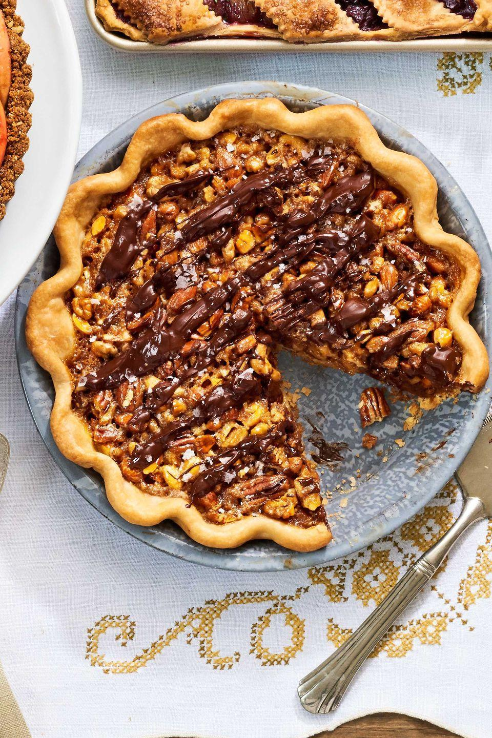 """<p>Dig into a chocolate-drizzled riff on classic pecan pie.</p><p><strong><a href=""""https://www.countryliving.com/food-drinks/recipes/a40044/maple-nut-pie-recipe/"""" rel=""""nofollow noopener"""" target=""""_blank"""" data-ylk=""""slk:Get the recipe"""" class=""""link rapid-noclick-resp"""">Get the recipe</a>.</strong> </p>"""