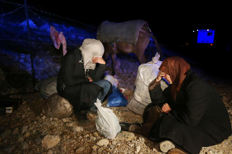 In this picture taken early Sunday, April 20, 2014, Samira Asrawi 45, right, and her daughter Marwa, 19, left, sit on the ground weeping next to their belongings as they wait to be vetted by Lebanese soldiers at an army check point after descending from 2,814-meter (9,232-foot) high Mount Hermon (Jabal el-Sheikh) and reached the town of Chebaa in southeast Lebanon. They were part of a group of around a dozen Syrians desperate to flee their country's bloody civil war who fled their home in the village of Beit Jinn, near the Israeli-occupied Golan Heights. They took part in a treacherous nighttime trek across the rugged frontier into neighboring Lebanon.(AP Photo/Hussein Malla)