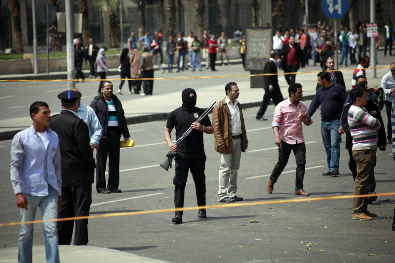 Egyptian security forces stand guard at the scene after multiple explosions hit the area outside the main campus of Cairo University, killing at least two, in Giza, Egypt, Wednesday, April 2, 2014. The bombings targeted riot police routinely deployed at the location in anticipation of near-daily protests by students who support ousted Islamist President Mohammed Morsi and his Muslim Brotherhood group. (AP Photo/Sabry Khaled, El Shorouk Newspaper) EGYPT OUT