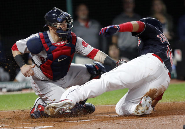 Boston Red Sox catcher Christian Vazquez, left, tags out Cleveland Indians' Edwin Encarnacion at home plate on a fielder's choice hit into by Josh Donaldson in the second inning of a baseball game, Sunday, Sept. 23, 2018, in Cleveland. (AP Photo/Tom E. Puskar)