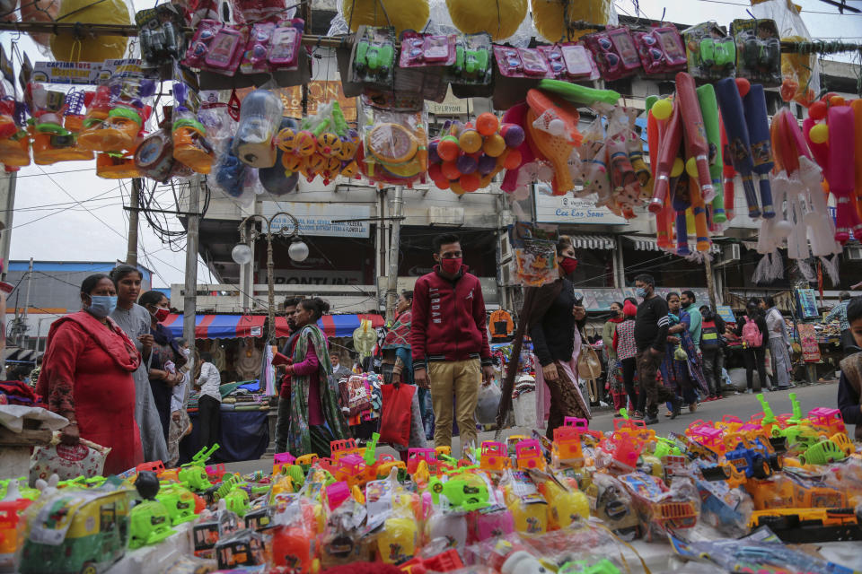 Indians, most of them, wearing face masks as a precautionary measure against the coronavirus walk at a Sunday market in Jammu, India, Sunday, Nov.22, 2020. (AP Photo/Channi Anand)