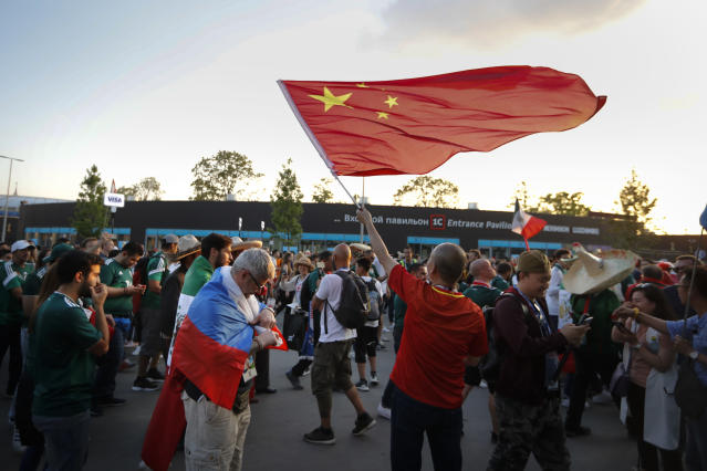 In this photo taken on Sunday, June 17, 2018, a Chinese soccer fan waves a China's national flag after the group F match between Germany and Mexico at the 2018 soccer World Cup in the Luzhniki Stadium in Moscow, Russia . Chinese sponsors are more visible than ever and tens of thousands of Chinese fans have descended on Moscow, using their growing economic clout to secure top-dollar seats and dreaming of the day, perhaps not that far off, when China will host football's showcase. (AP Photo/Alexander Zemlianichenko)