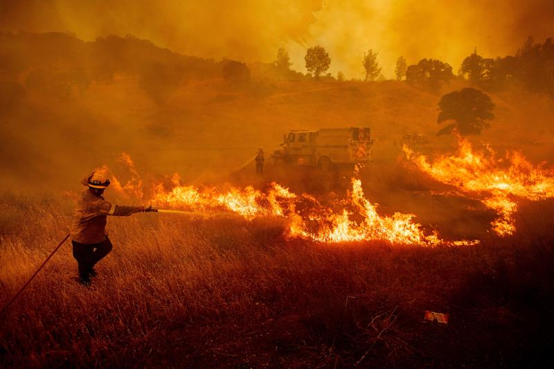 July 1, 2018: A firefighter scrambles to stop a wildfire as wind drives embers across Highway 20 near Clearlake Oaks, Calif.