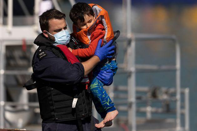 A young migrant being carried by a Border Force official after arriving into Dover on Wednesday (Photo: Dan Kitwood via Getty Images)