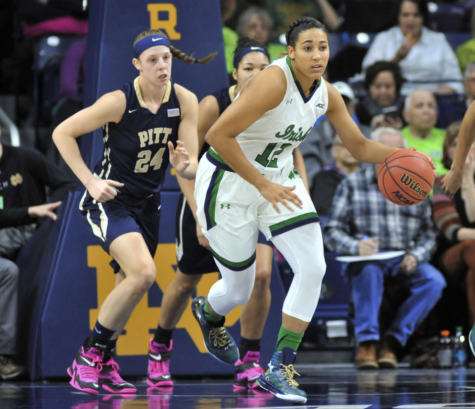 Notre Dame forward Taya Reimer (12) brings the ball up as Pittsburgh forward Monica Wignot (24) gives chase during the first half of an NCAA college basketball game Thursday, Feb. 26, 2015, in South Bend, Ind. (AP Photo/Joe Raymond)