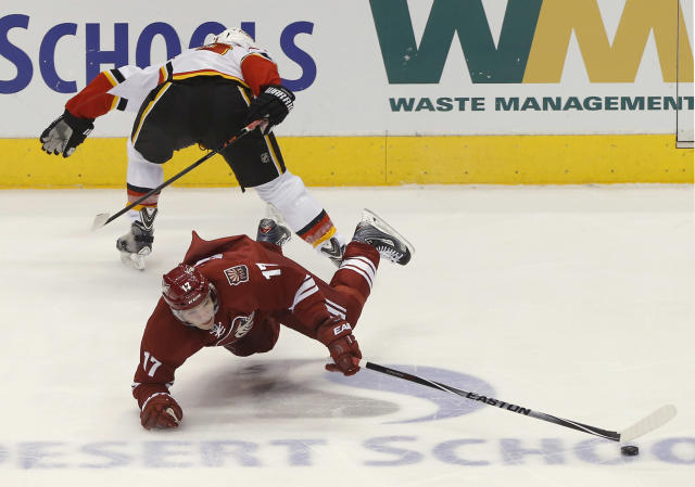 Calgary Flames' Mark Giordano, top, trips Phoenix Coyotes' Radim Vrbata (17) for a penalty during the second period of NHL hockey game, Saturday, March 15, 2014, in Glendale, Ariz. (AP Photo/Matt York)