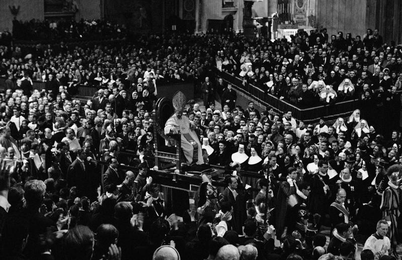 FILE - In this Feb. 25, 1965 file photo Pope Paul VI is borne on his portbale throne, the Sedia Gestatoria, through a huge crowd in St. Peter's Basilica, at the Vatican. Watching Pope Francis in his first papal appearances, he too doesn't look the type to be carried on a portable throne. After all, he used to take the bus to work as a cardinal back in Buenos Aires, and he eschewed the chauffeur-driven Vatican limousine when he made his first outing, using a simple Vatican car. Change comes slowly, hesitantly and inconsistently at the Vatican. (AP Photo)