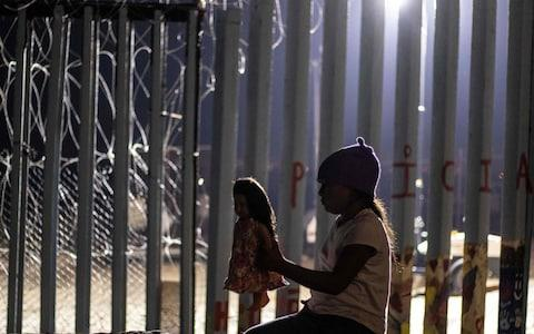A girl from Guatemala, part of the Central American migrant caravan, plays with a doll near the US-Mexico border fence - Credit: AFP