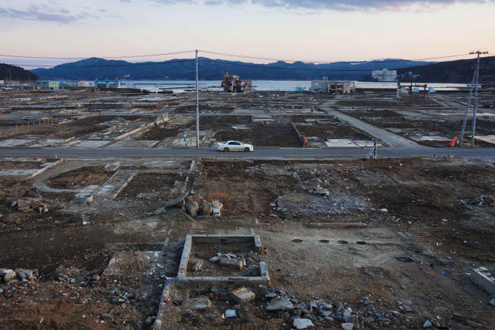 In this Feb. 23, 2012, file photo, a car passes through the leveled city of Minamisanriku, Miyagi Prefecture, northeastern Japan, almost one year after the March 11 tsunami. (AP Photo/David Guttenfelder, File)