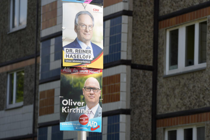 Election campaign posters from Merkel's Christian Democratic Union, CDU, with top candidate and state governor Reiner Haseloff, top, and from the far-right Alternative for Germany, AFD, party with top candidate, Oliver Kirchner, displayed in front of a residents building at federal state Saxony-Anhalt's capital Magdeburg, Germany, Wednesday, June 2, 2021.The state vote on Sunday, June 6, 2021 is German politicians' last major test at the ballot box before the national election in September that will determine who succeeds Chancellor Angela Merkel. (AP Photo/Markus Schreiber)