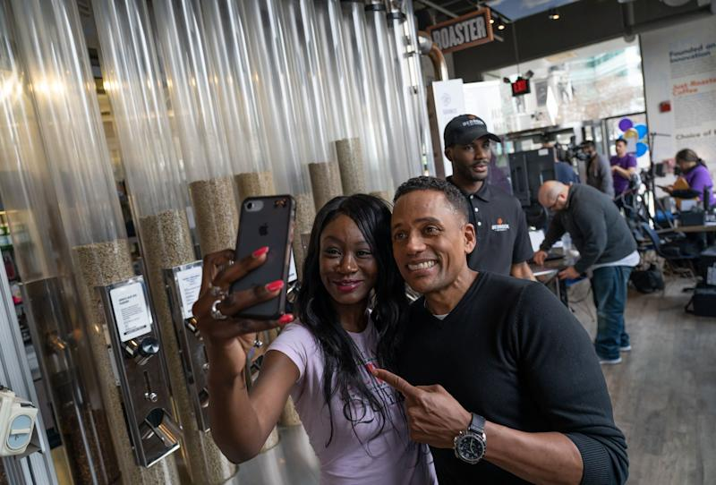 """Shamika Robinson of Detroit takes a selfie with actor Hill Harper as he does promotion about """"Credit over Coffee"""" as part of an effort to build credit scores through a new program called Experian Boost at his business the Roasting Plant Coffee in downtown Detroit on Wednesday, May 1, 2019."""