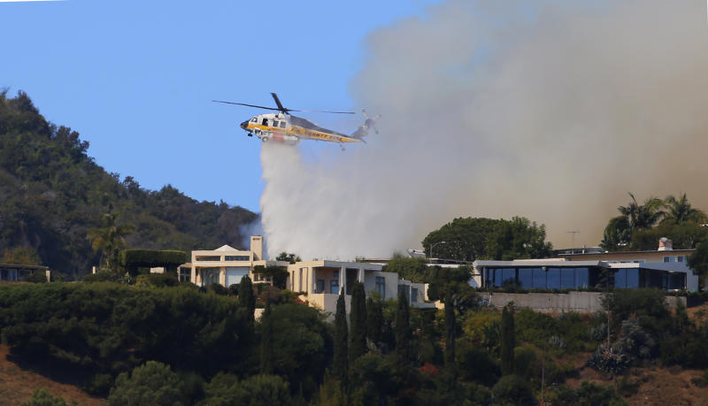 A helicopter makes a water drop as flames threaten homes on a ridgeline as a wildfire threatens homes in the Pacific Palisades area of Los Angeles, Monday, Oct. 21, 2019. (AP Photo/Reed Saxon)