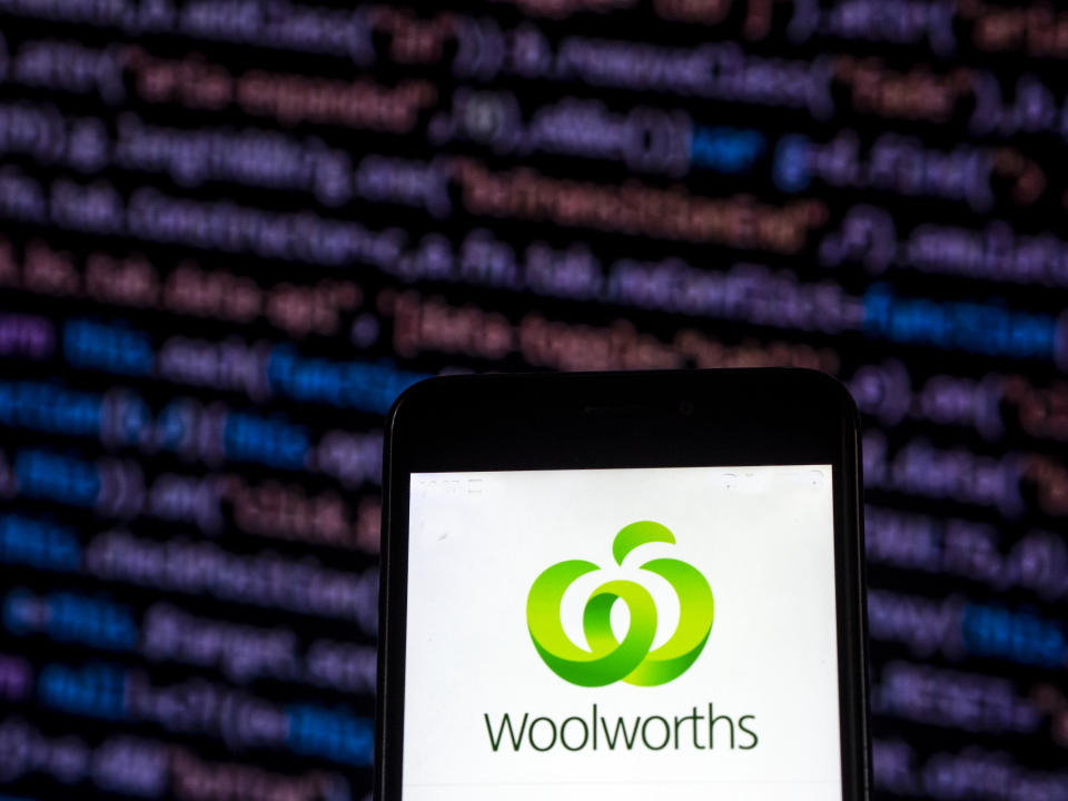 Woolworths app on phone in front of coding screen on computer. Source: Getty Images