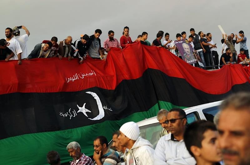 Libyans hold a large version of their national flag during a demonstration against power-sharing agreement proposed by UN envoy Bernardino Leon in the centre of the eastern coastal Libyan city of Benghazi on October 23, 2015