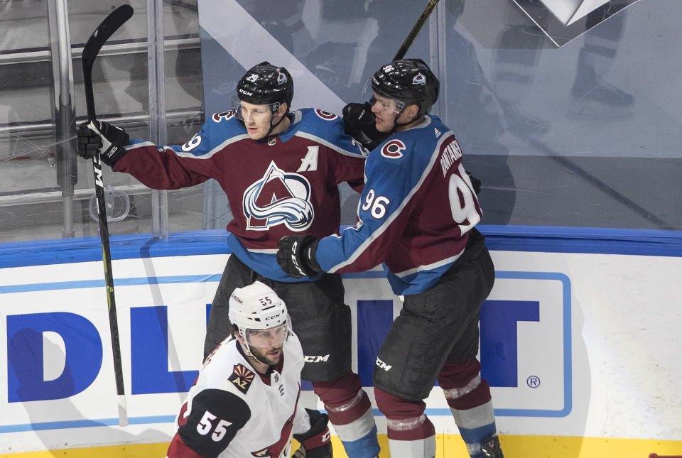 Colorado Avalanche' Nathan MacKinnon (29) and Mikko Rantanen (96) celebrate a goal as Arizona Coyotes' Jason Demers (55) skates past during the first period of a first round NHL Stanley Cup playoff hockey series in Edmonton, Alberta, Friday, Aug. 14, 2020. (Jason Franson/The Canadian Press via AP)