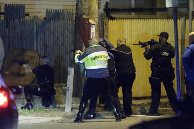 Police officers aim their weapons Friday, April 19, 2013, in Watertown, Mass. A tense night of police activity that left a university officer dead on campus just days after the Boston Marathon bombings and amid a hunt for two suspects caused officers to converge on a neighborhood outside Boston, where residents heard gunfire and explosions.(AP Photo/Matt Rourke)