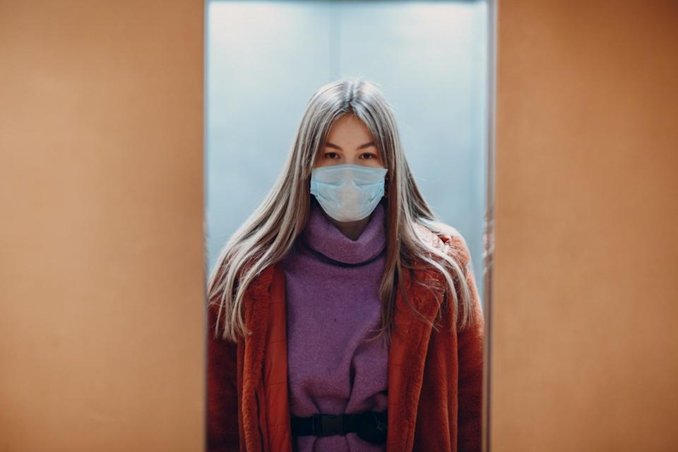 Young chinese woman standing in elevator in medical mask. Doors are closing. Coronavirus COVID-19 pandemic concept.