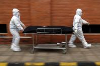 Nurses take the body of Isidra Coronel to the morgue after removing her body from a hospital bed where she died from the new coronavirus at Hospital de Clinicas in San Lorenzo, Paraguay, Friday, June 18, 2021. A coronavirus wave has resulted in a flood of patients infected with the virus overwhelming intensive care units and a surge in the country's COVID-19 death toll. (AP Photo/Jorge Saenz)