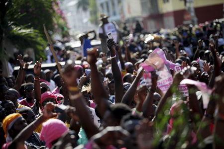 Supporters of PHTK political party react to a speech next to the Provisional Electoral Council building during a demonstration to demand the organization of a postponed presidential runoff election in Port-au-Prince, Haiti, April 24, 2016. REUTERS/Andres Martinez Casares