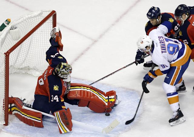 Florida Panthers goalie Tim Thomas (34) stops the puck as New York Islanders' John Tavares (91) attempts a shot on the goal during the second period of an NHL hockey game, Tuesday, Jan. 14, 2014, in Sunrise, Fla. (AP Photo/Lynne Sladky)