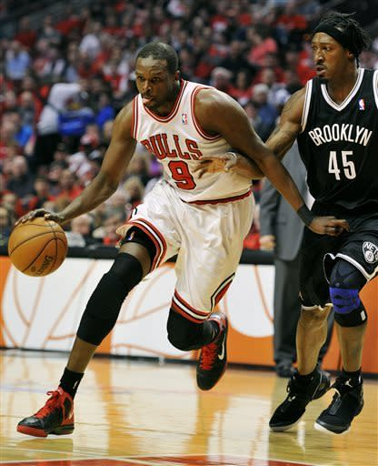 Chicago Bulls' Luol Deng (9) drives to the basket around Brooklyn Nets' Gerald Wallace (45) during the first half in Game 4 of their first-round NBA basketball playoff series Saturday, April 27, 2013, in Chicago. (AP Photo/Jim Prisching)