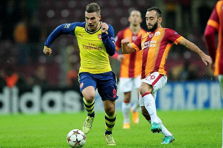 Arsenal's Lucas Podolski (L) stroms past Galatasaray's Olcan Adin during their UEFA Champions League group D match at TT Arena Stadium on December 9, 2014 in Istanbul (AFP Photo/Ozan Kose)