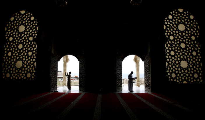 A Palestinian man, right, reads verses of the Quran, Islam's holy book, on one of the last days of the month of Ramadan, at Al Khaldi mosque in Gaza City, Saturday, May 9, 2021. (AP Photo/Hatem Moussa)