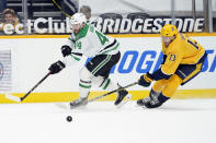 Dallas Stars defenseman Joel Hanley (44) and Nashville Predators center Yakov Trenin (13) battle for the puck in the second period of an NHL hockey game Sunday, April 11, 2021, in Nashville, Tenn. (AP Photo/Mark Humphrey)